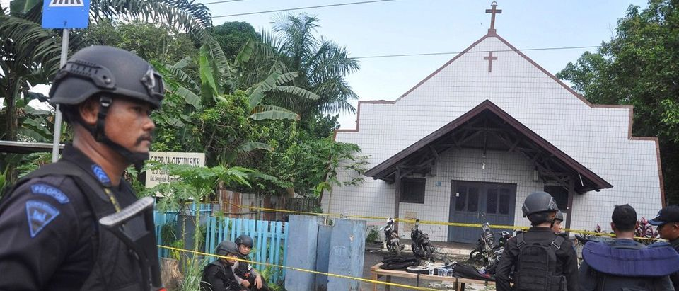 Police stand near the scene of an explosion outside a church in Samarinda, East Kalimantan, Indonesia