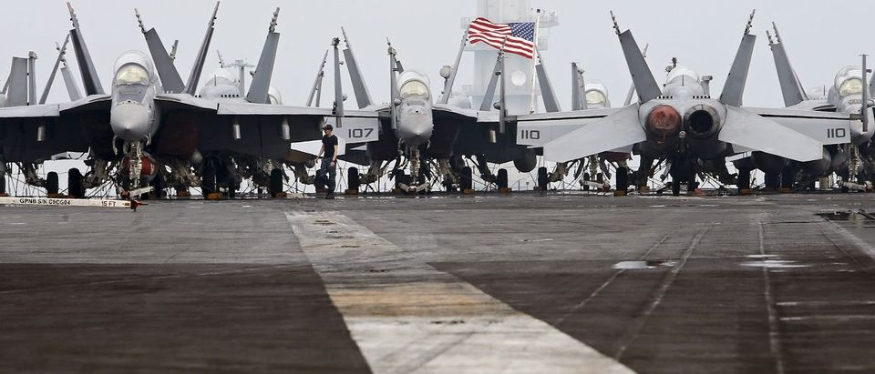 A U.S. Navy personnel walks amongst F/A-18 aircraft onboard the flight deck of the USS Theodore Roosevelt at Changi Navy Base in Singapore