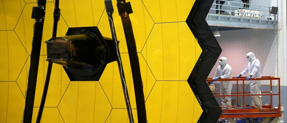 NASA workers are lifted alongside the James Webb Space Telescope Mirror during it's media reveal at NASAs Goddard Space Flight Center at Greenbelt