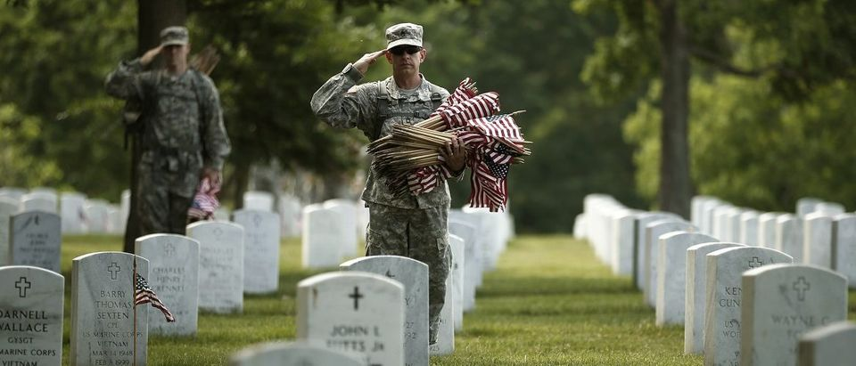 Soldiers place flags for Memorial Day at Arlington National Cemetery in Virginia