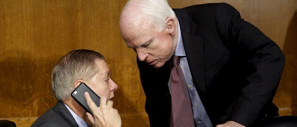 Senator McCain talks to Senator Graham at Senate Armed Services Committee in Washington