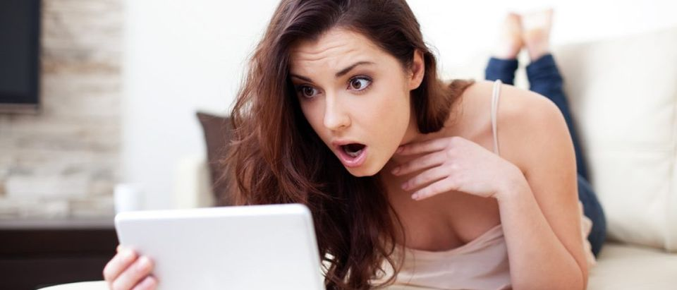 Woman surprised after finding out about a recent hack. [Shutterstock - baranq]