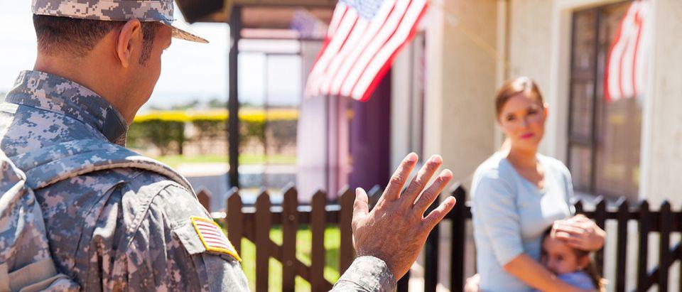 Military serviceman waving to family