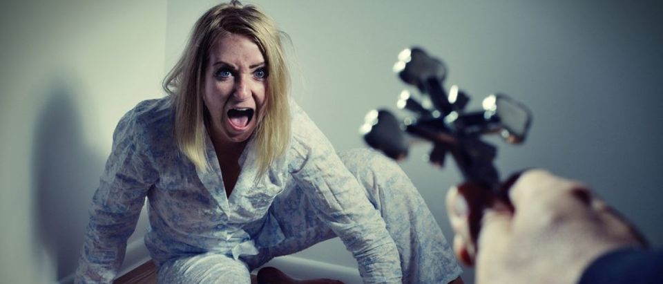 Casting out a demon from a woman through prayer. Exorcisms over deranged and crazy person. (Photo via Shutterstock)