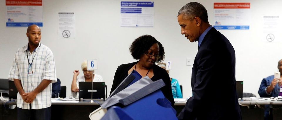 A poll worker assists Obama as he prepares to cast his vote for president in early voting at the Cook County Office Building in Chicago