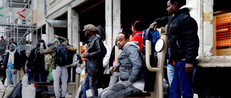 Migrants wait for a bus to leave the reception center for migrants and refugees near porte de La Chapelle in the north of Paris