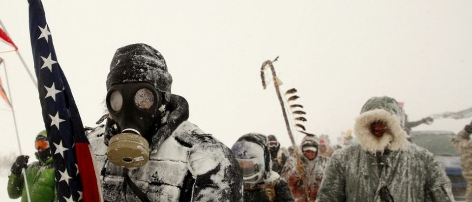 "A man takes part in a march with veterans to Backwater Bridge just outside of the Oceti Sakowin camp during a snow fall as ""water protectors"" continue to demonstrate against plans to pass the Dakota Access pipeline adjacent to the Standing Rock Indian Reservation, near Cannon Ball, North Dakota, U.S., December 5, 2016. REUTERS/Lucas Jackson"