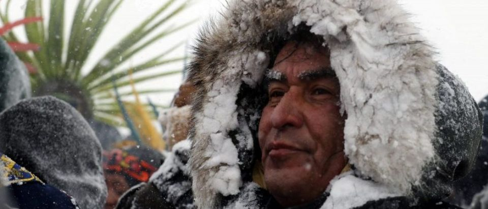 "A Native American man stands in the snow during a march with veterans near Backwater Bridge just outside of the Oceti Sakowin camp during a snow fall as ""water protectors"" continue to demonstrate against plans to pass the Dakota Access pipeline adjacent to the Standing Rock Indian Reservation, near Cannon Ball, North Dakota, U.S., December 5, 2016. REUTERS/Lucas Jackson"