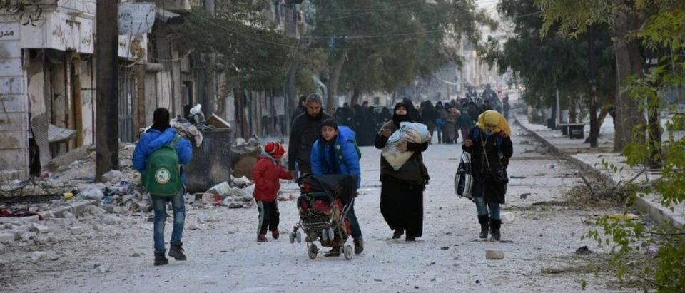 People, who evacuated the eastern districts of Aleppo, carry their belongings as they arrive in a government held area of Aleppo