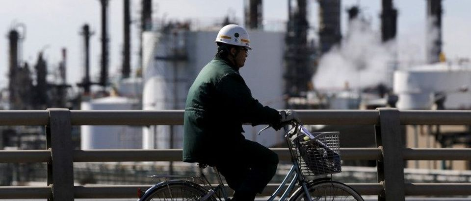 A worker cycles near a factory at the Keihin industrial zone in Kawasaki, Japan