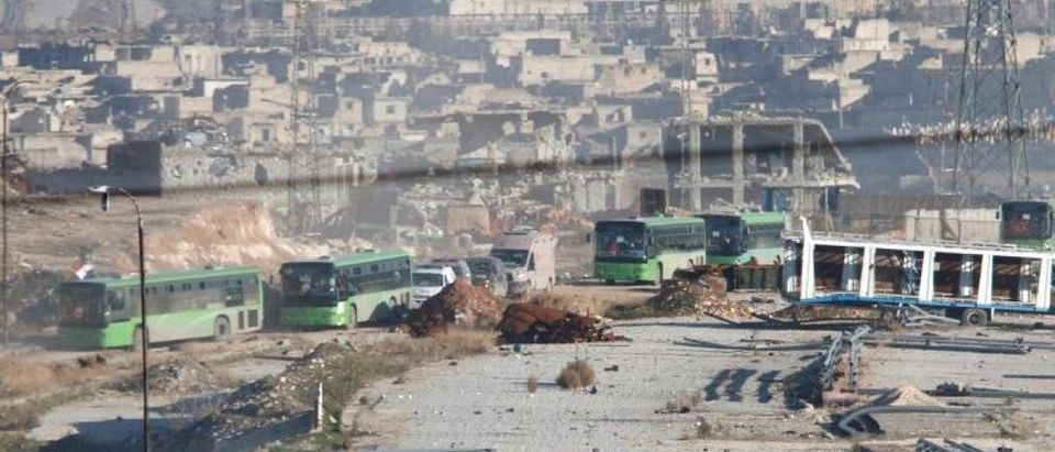 Ambulances and buses evacuating people drive out of a rebel-held part of Aleppo