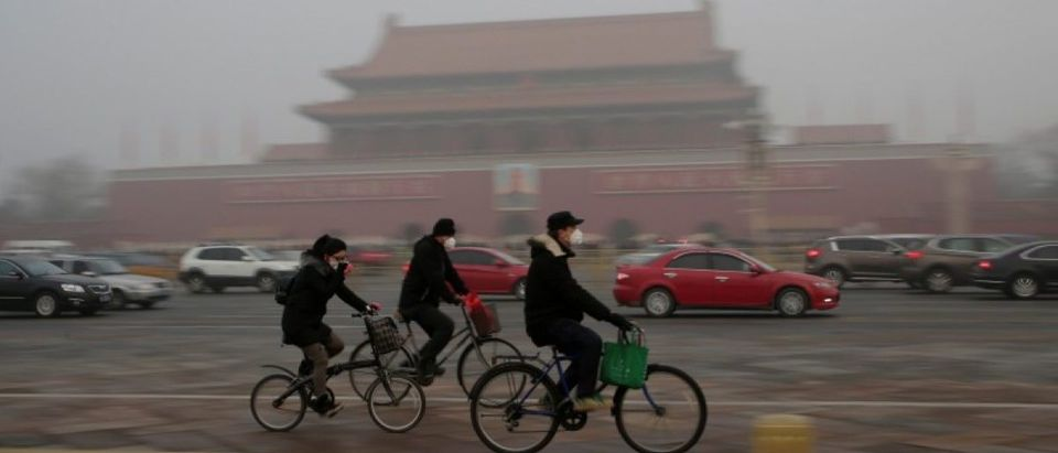 People wearing masks cycle past Tiananmen Gate during the smog in Beijing