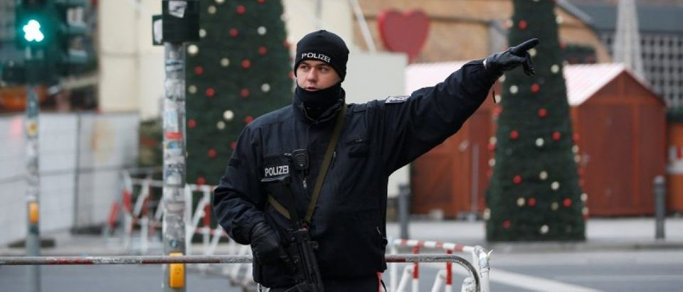 A policeman gestures near the scene where a truck ploughed into a crowded Christmas market in the German capital last night in Berlin