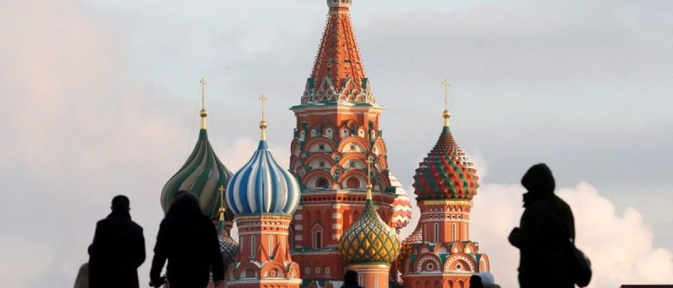 FILE PHOTO: People walk in Red Square, with St. Basil's Cathedral seen in the background, in central Moscow