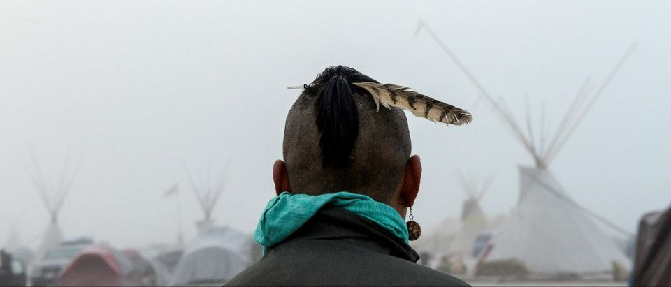 A man from the Muskogee tribe looks at the Oceti Sakowin shrouded in mist during a protest against the Dakota Access pipeline near the Standing Rock Indian Reservation near Cannon Ball, North Dakota, U.S. November 11, 2016. REUTERS/Stephanie Keith