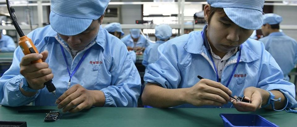 This picture taken on April 22, 2015 shows Chinese workers assembling a cheaper local alternative to the Apple Watch in a factory producing thousands every day in Shenzhen, in southern China's Guangdong province. (Photo credit: STR/AFP/Getty Images)