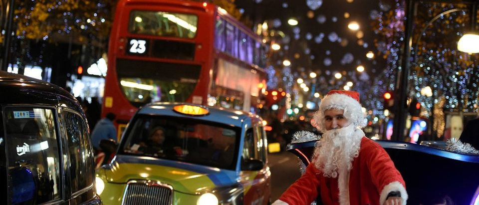 A man dressed as Santa Claus cycles on Oxford Street, which is illuminated with Christmas lights, in London, Britain, December 9, 2016. REUTERS/Clodagh Kilcoyne