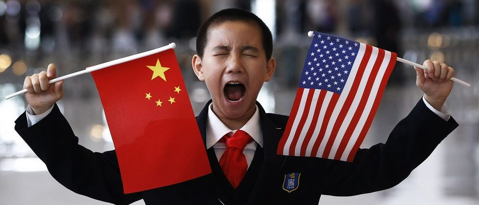 A boy who is waiting to greet U.S. Secretary of State Clinton at the National Museum makes a face while holding the U.S. and Chinese flags in Beijing