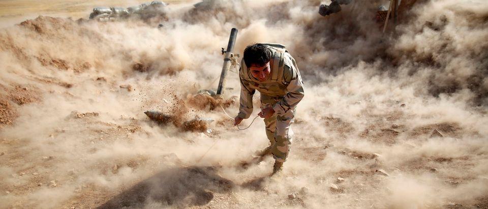 A Kurdish Peshmerga fighter launches mortar shells towards Zummar, controlled by Islamic State, near Mosul