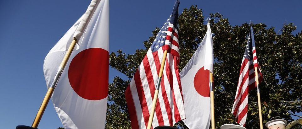 An honor guard carries U.S. and Japanese flags during official arrival ceremony for Japanese Prime Minister Abe at the White House in Washington