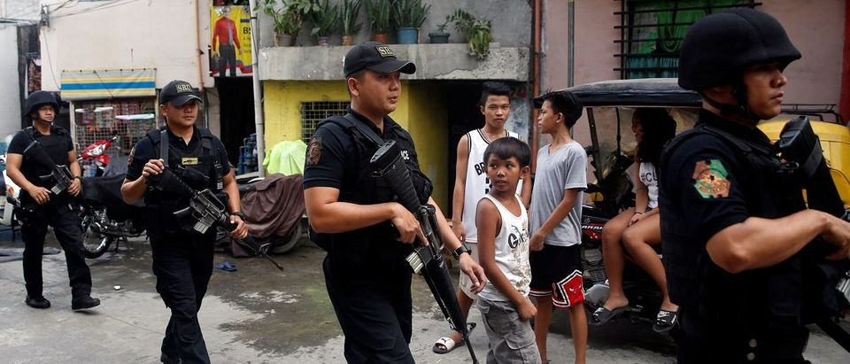 Members of Philippine National Police's SWAT team hold their weapons as they walk past residents during an anti-drugs operation in Mandaluyong