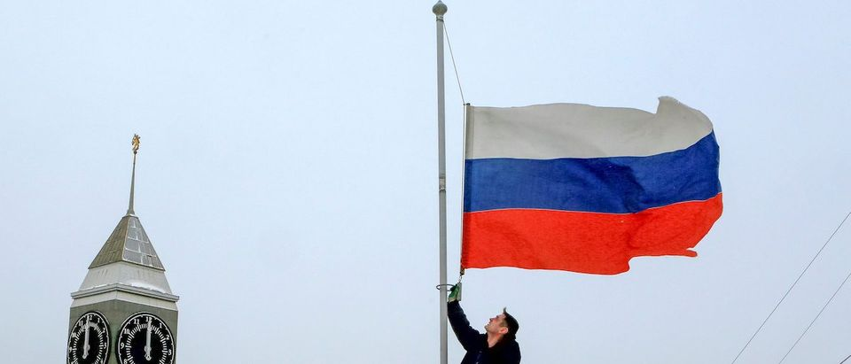 A worker lowers the Russian national flag to half-mast on a roof of the city administration building, as the country observes a day of mourning for victims of the Tu-154 plane which crashed into the Black Sea on its way to Syria on Sunday, in Krasnoyarsk