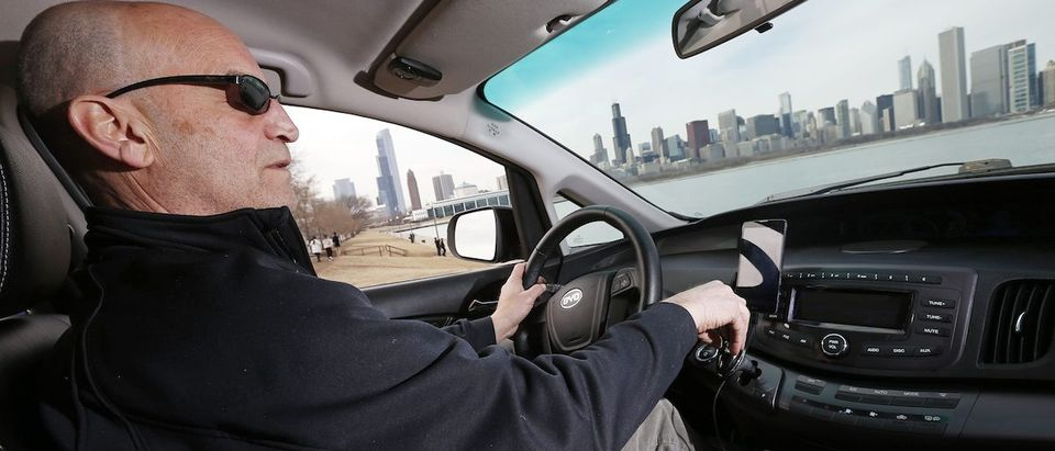 Uber driver Glen Snower sits in a BYD e6 electric car in Chicago