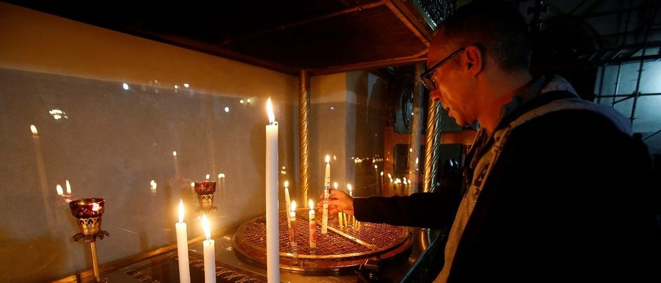 Visitor lights a candle inside the Church of the Nativity in the West Bank town of Bethlehem