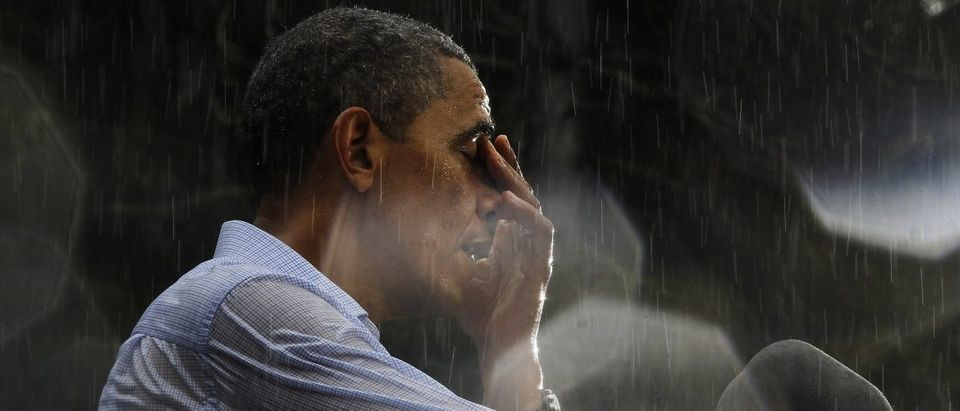 U.S. President Barack Obama wipes water off his face during a rain shower at a campaign rally in Glen Allen