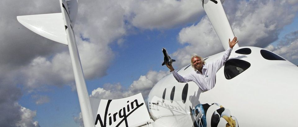 Entrepreneur Richard Branson waves a model of the LauncherOne cargo spacecraft from a window of an actual size model of SpaceShipTwo on display, after Virgin Galactic's LauncherOne announcement and news conference, at the Farnborough Airshow 2012