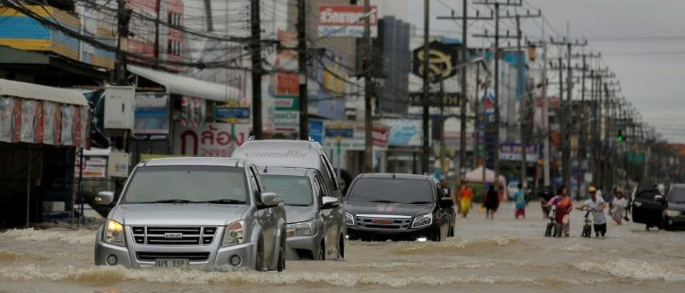 Cars drive through a flooded street at Muang district in Nakhon Si Thammarat province