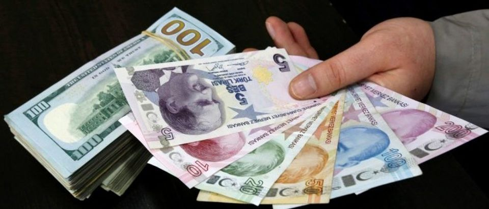 FILE PHOTO - A money changer holds Turkish lira banknotes next to U.S. dollar bills at a currency exchange office in central Istanbul