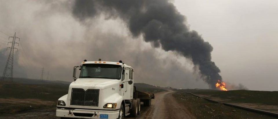Thick smoke rises as a fire breaks out at oil wells set ablaze by Islamic State militants before fleeing the oil-producing region of Qayyara
