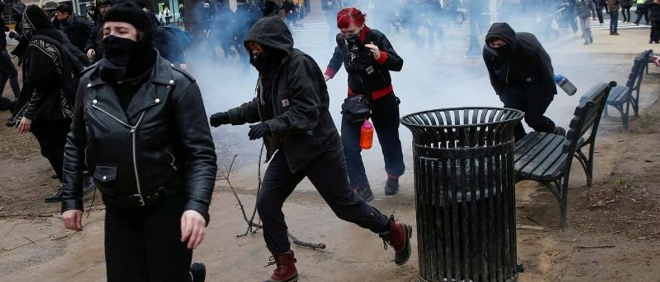 Activists race after being hit by a stun grenade while protesting against U.S. President-elect Donald Trump on the sidelines of the inauguration in Washington