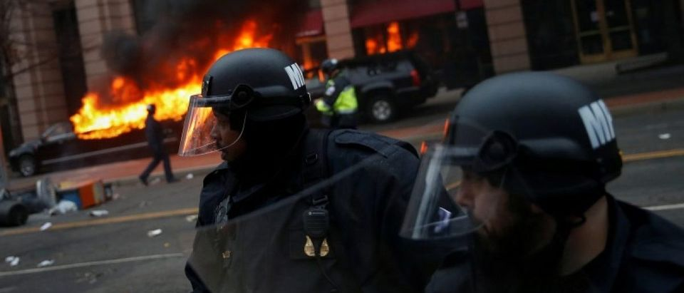 Police stand near burning limousine during protest against Trump on sidelines of inauguration in Washington, D.C., U.S.,