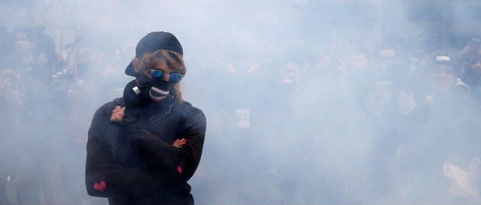 An activist stands amid smoke from a stun grenade while protesting against U.S. President Donald Trump on the sidelines of the inauguration in Washington