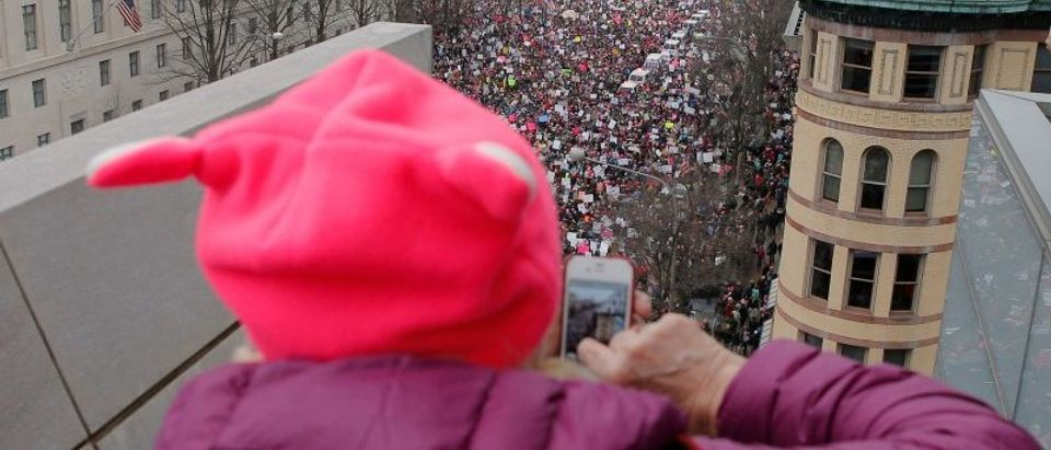 A woman wearing a pink pussy protest hat takes a photograph of the Women's March on Washington, following the inauguration of U.S. President Donald Trump, in Washington