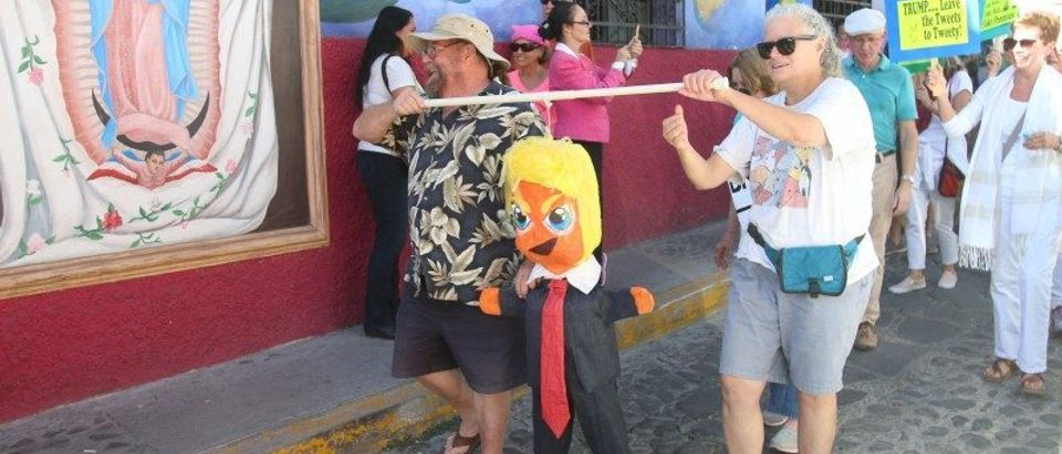 People carry a pinata representing U.S. President Donald Trump during an event organized by American expats and Canandian nationals, in solidarity with the Washington's Women's March, in Ajijic