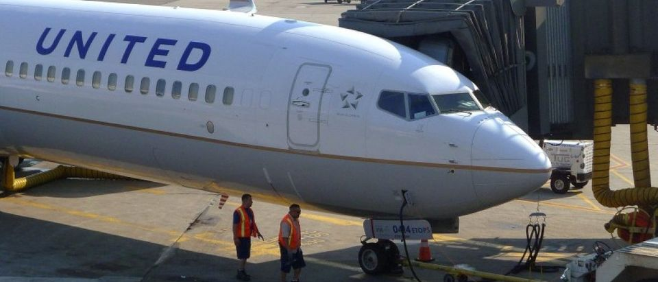 FILE PHOTO - Two ground crew members walk past a United Airlines airplane as it sits at a gate at Newark Liberty International Airport