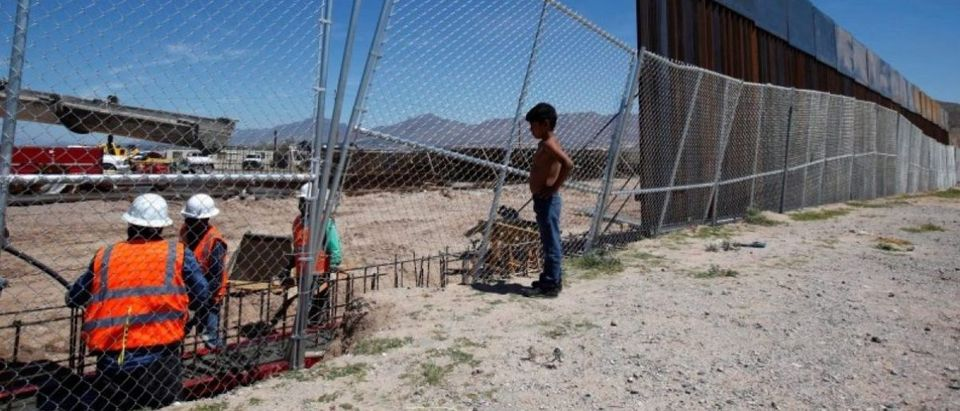 A boy looks at U.S. workers building a section of the U.S.-Mexico border wall at Sunland Park, U.S. opposite the Mexican border city of Ciudad Juarez