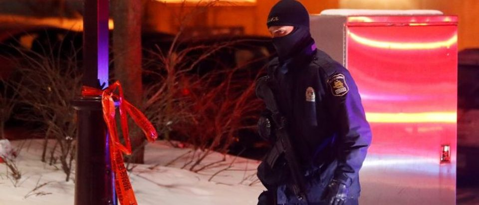 A police officer patrols the perimeter near a mosque after a shooting in Quebec City