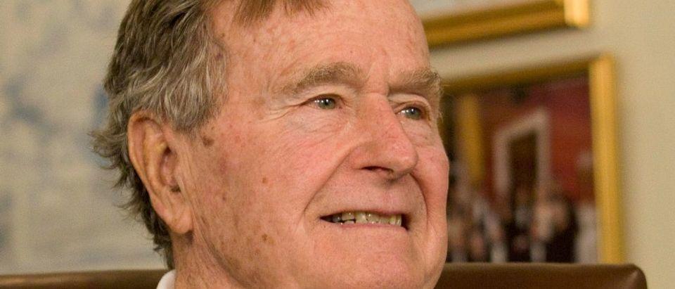FILE PHOTO - Former President Bush smiles as he listens to Republican presidential candidate Romney speak in Houston