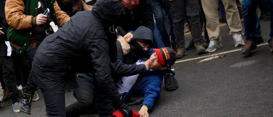 A protester chokes a Trump supporter as they attempt to steal his Trump hat - Daily Caller - Grae Stafford