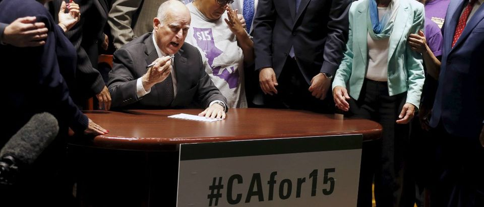 California Governor Jerry Brown (C) signs a bill hiking California's minimum wage to $15 by 2023 in Los Angeles, California, United States, April 4, 2016. REUTERS/Lucy Nicholson