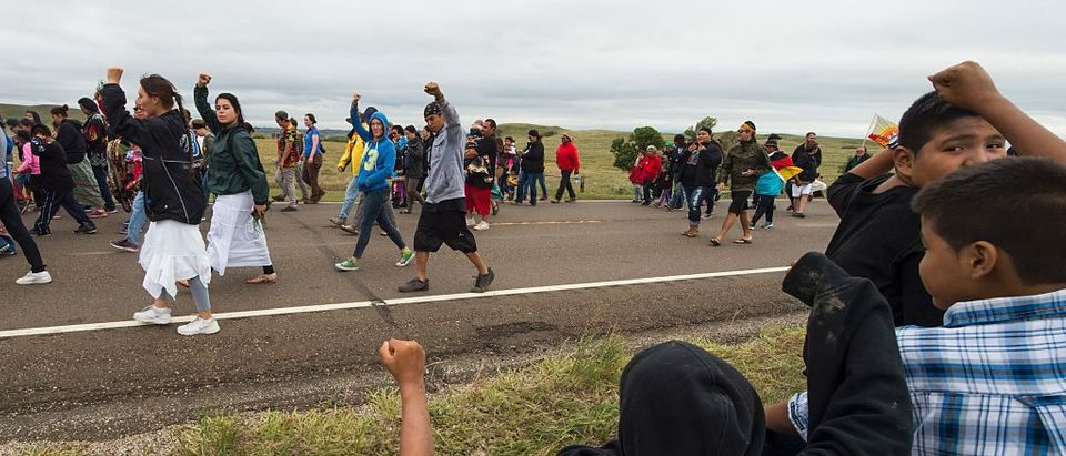 Hundreds of Native Americans march to a burial ground sacred site that was disturbed by bulldozers building the Dakota Access Pipeline (DAPL), near the encampment where hundreds of people have gathered to join the Standing Rock Sioux Tribe's protest of the oil pipeline that is slated to cross the Missouri River nearby, September 4, 2016 near Cannon Ball, North Dakota.