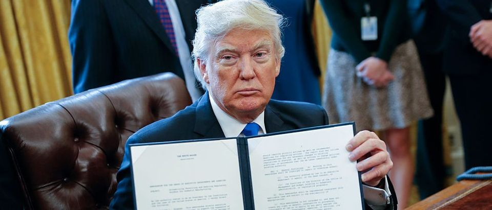 President Donald Trump displays one of five executive orders he signed related to the oil pipeline industry in the Oval Office of the White House January 24, 2017 in Washington, D.C. (Photo by Shawn Thew-Pool/Getty Images)