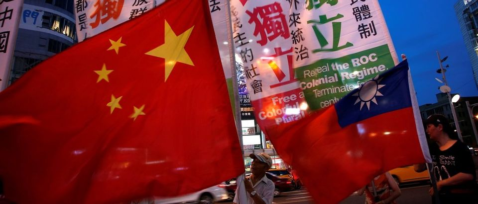 Members of a Taiwanese independence group march with flags around a group of pro-China supporters holding a rally calling for peaceful reunification in Taipei, Taiwan