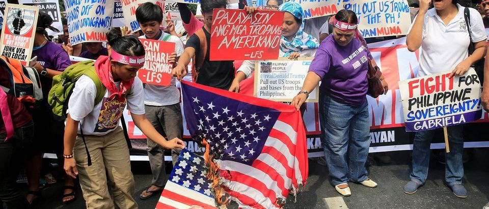 Protesters burn a U.S. flag and a mock flag with pictures of U.S. President-elect Donald Trump outside the U.S. embassy in metro Manila