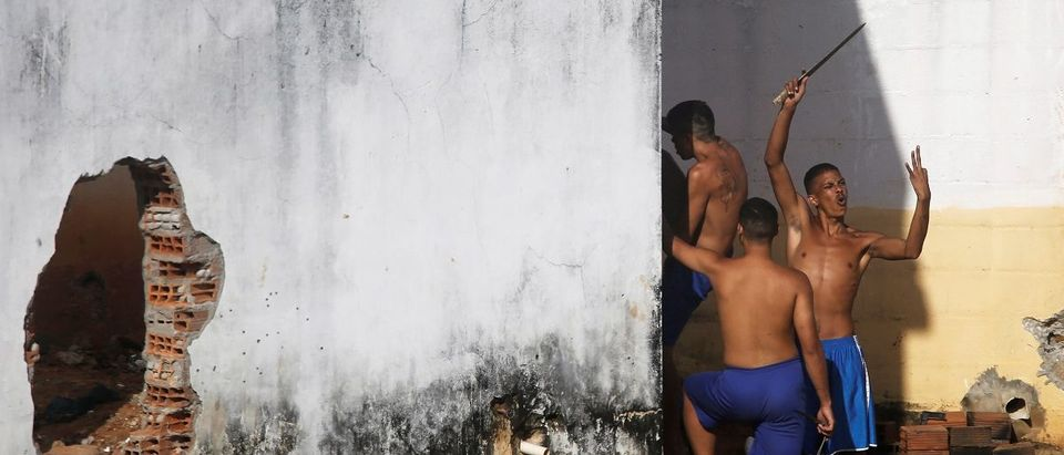 An inmate gestures after riot policemen did a head count of them during an uprising at Alcacuz prison in Natal