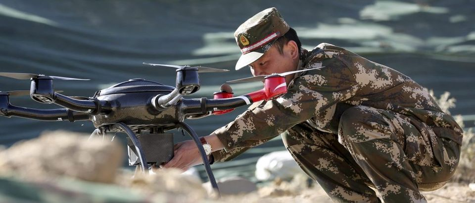 A police officer prepares a drone for display during a drill at a military base in Shigatse